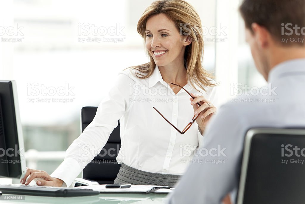 Smiling female manager at workplace stock photo