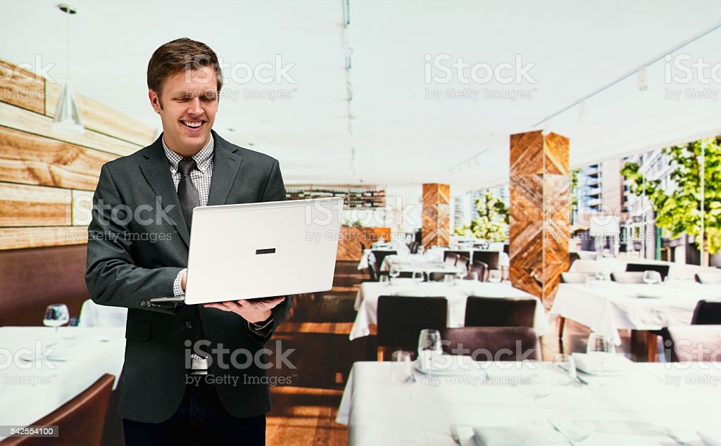 Smiling business owner working on laptop stock photo