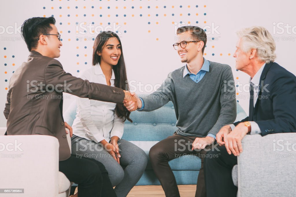 Smiling Business Partners Shaking Hands in Lounge stock photo