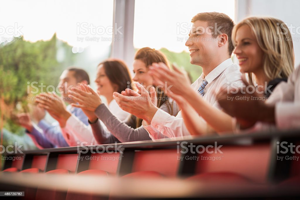 Smiling business people applauding on a conference. stock photo