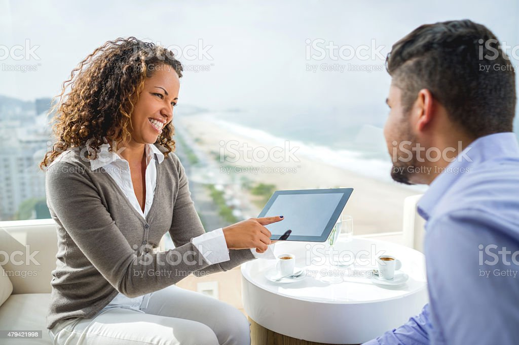 Smiling business people communicating and using touchpad. stock photo