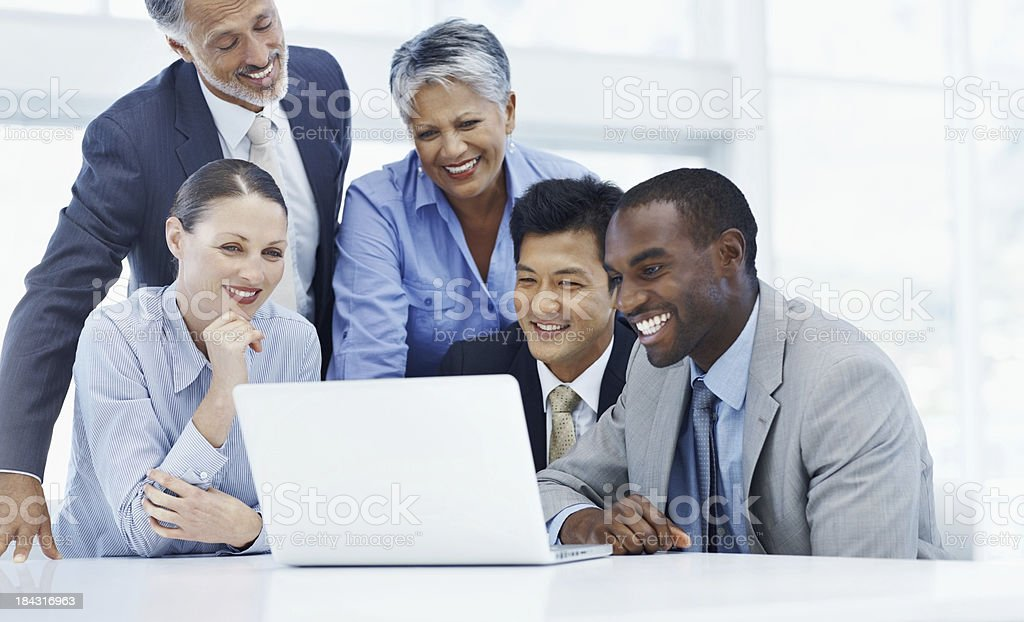 Smiling business people looking at laptop royalty-free stock photo
