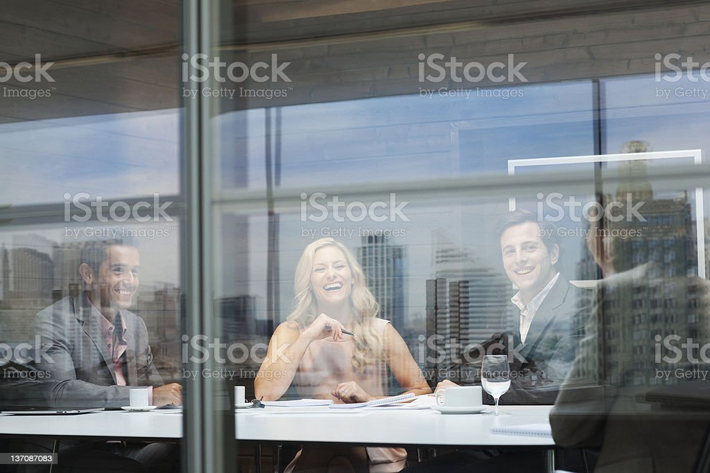 Smiling business people meeting at conference room table stock photo