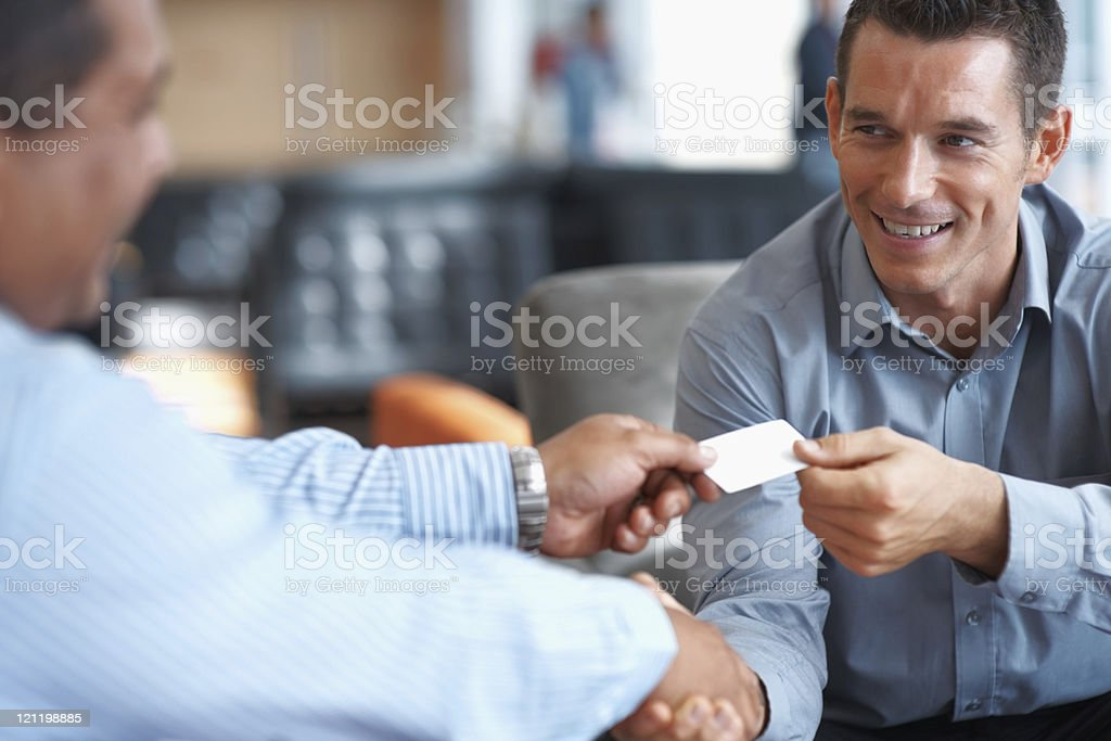 Smiling business people shaking hands at office stock photo