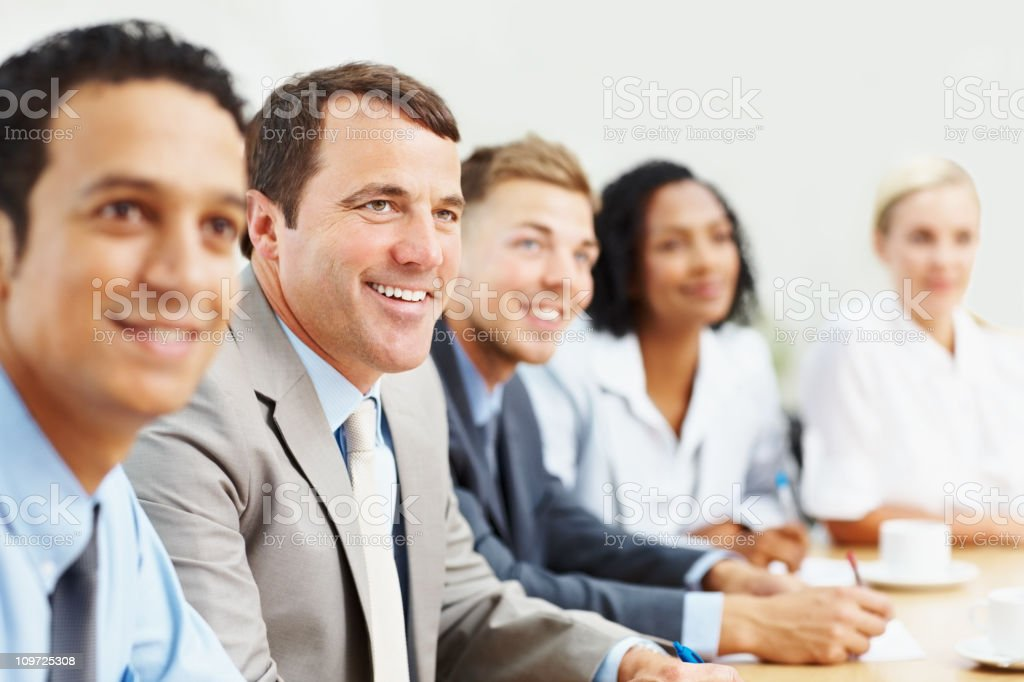 Smiling business people sitting at a meeting royalty-free stock photo