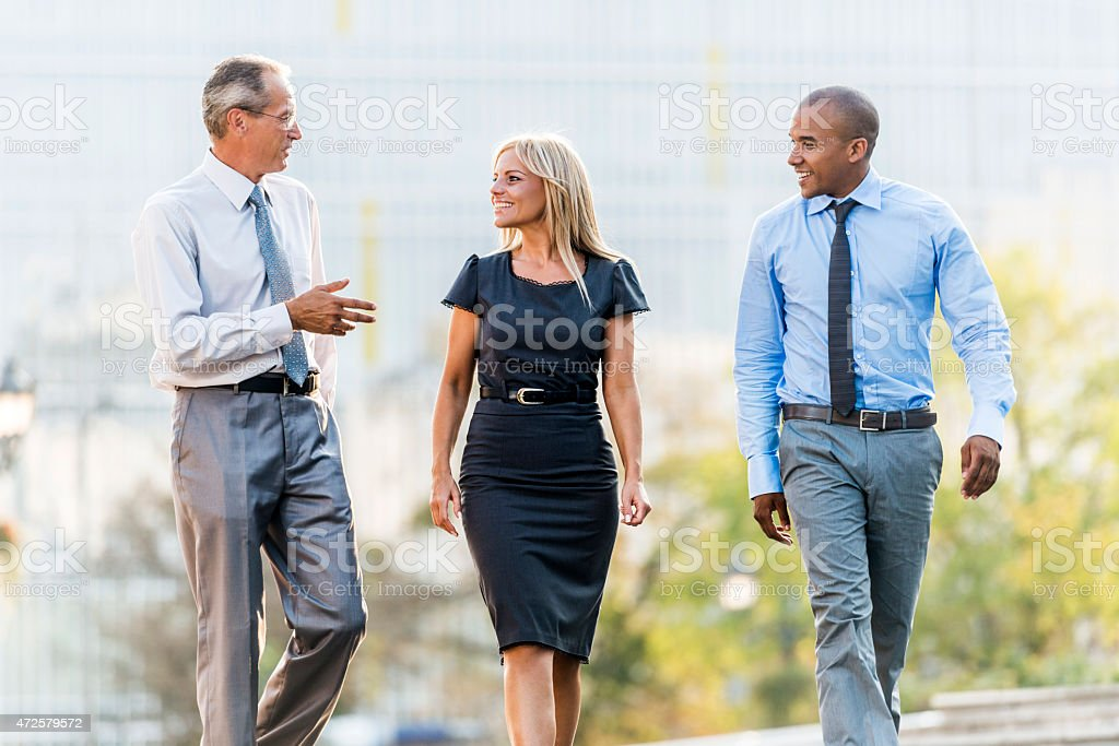 Smiling business people walking in the street and communicating. stock photo