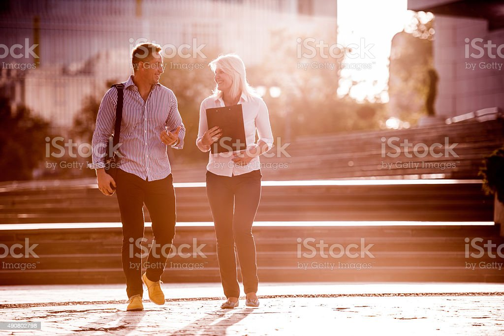 Smiling business people walking on the street and communicating. stock photo