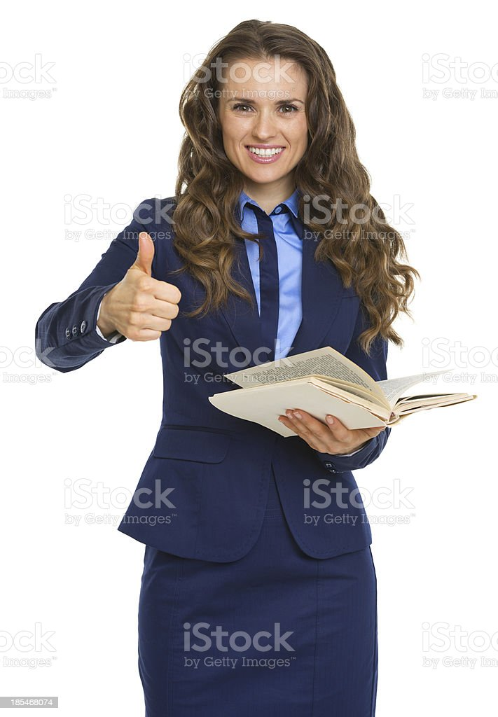 Smiling business woman holding book and showing thumbs up royalty-free stock photo