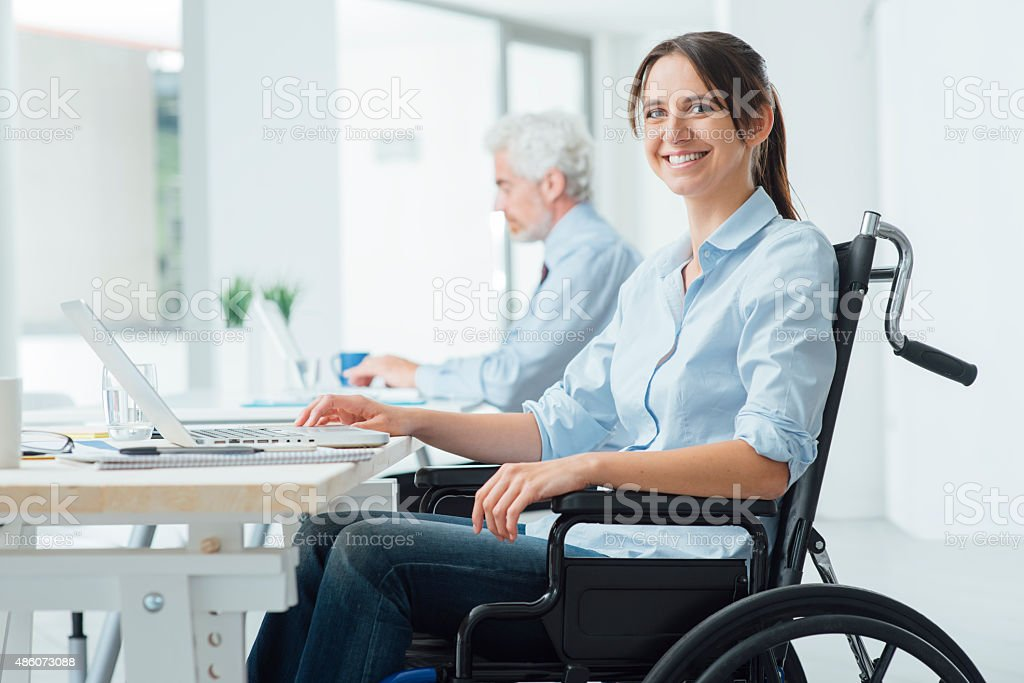 Smiling business woman in wheelchair stock photo
