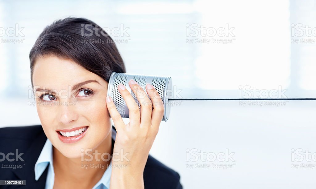 Smiling business woman listening to a tin can telephone stock photo