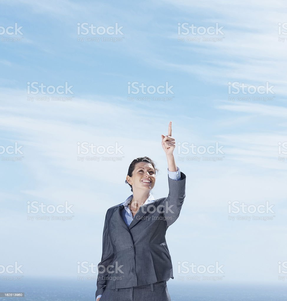 Smiling business woman pointing upwards at copyspace royalty-free stock photo