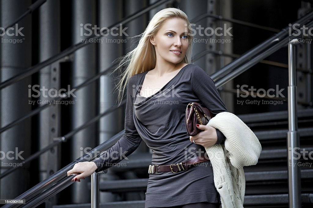 smiling business woman posing on stairs of  office building stock photo