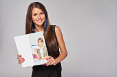 Smiling business woman showing advertising brochure