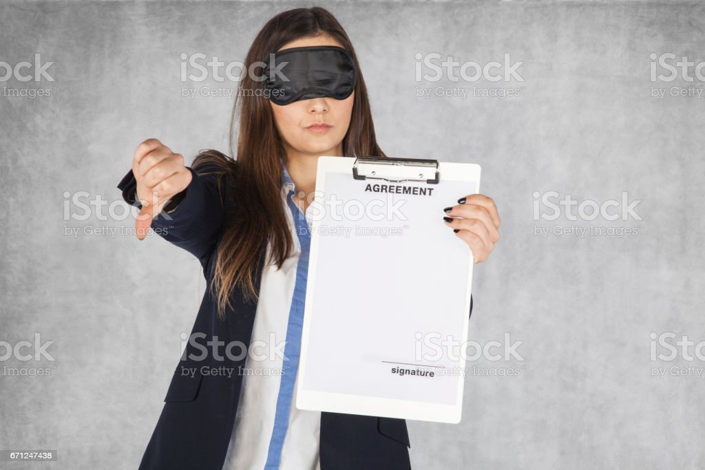 Smiling business woman shows thumb upwards, blindfolded stock photo