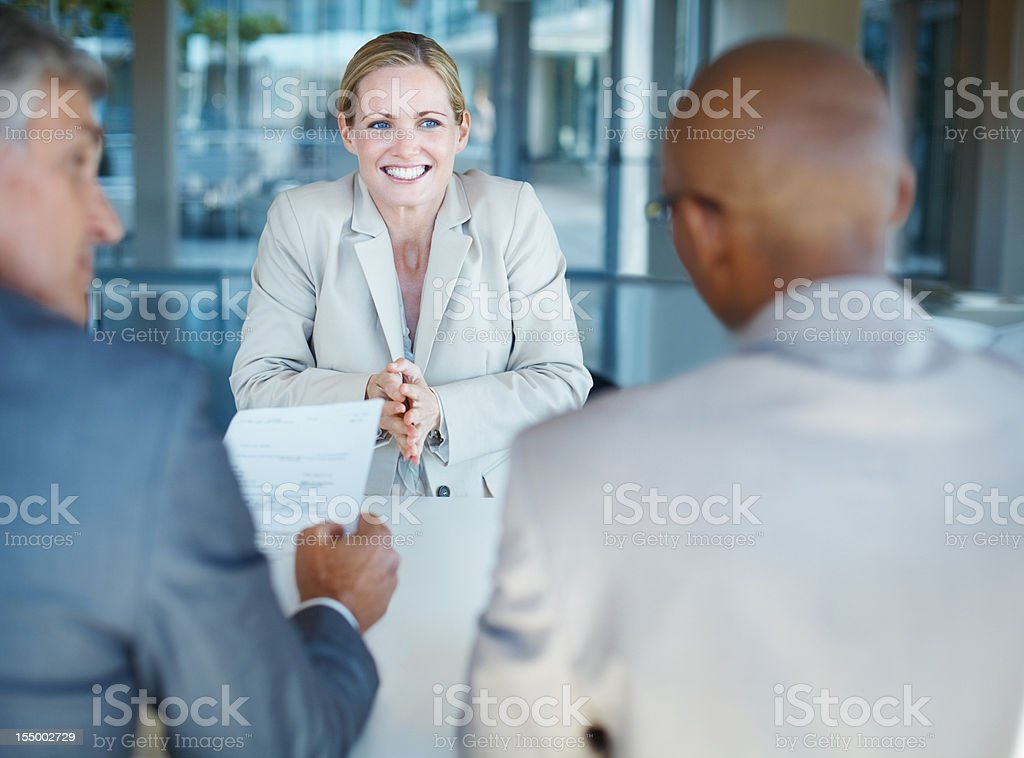 Smiling business woman sitting in front of interviewers royalty-free stock photo
