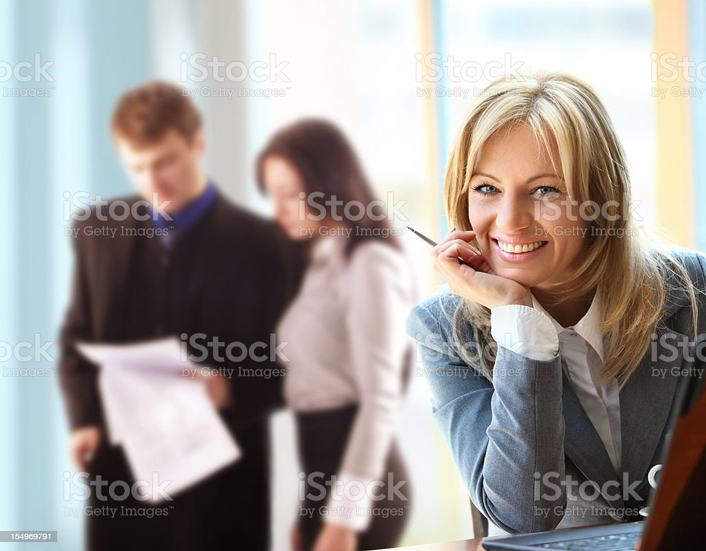 Smiling business woman with associates in background. stock photo