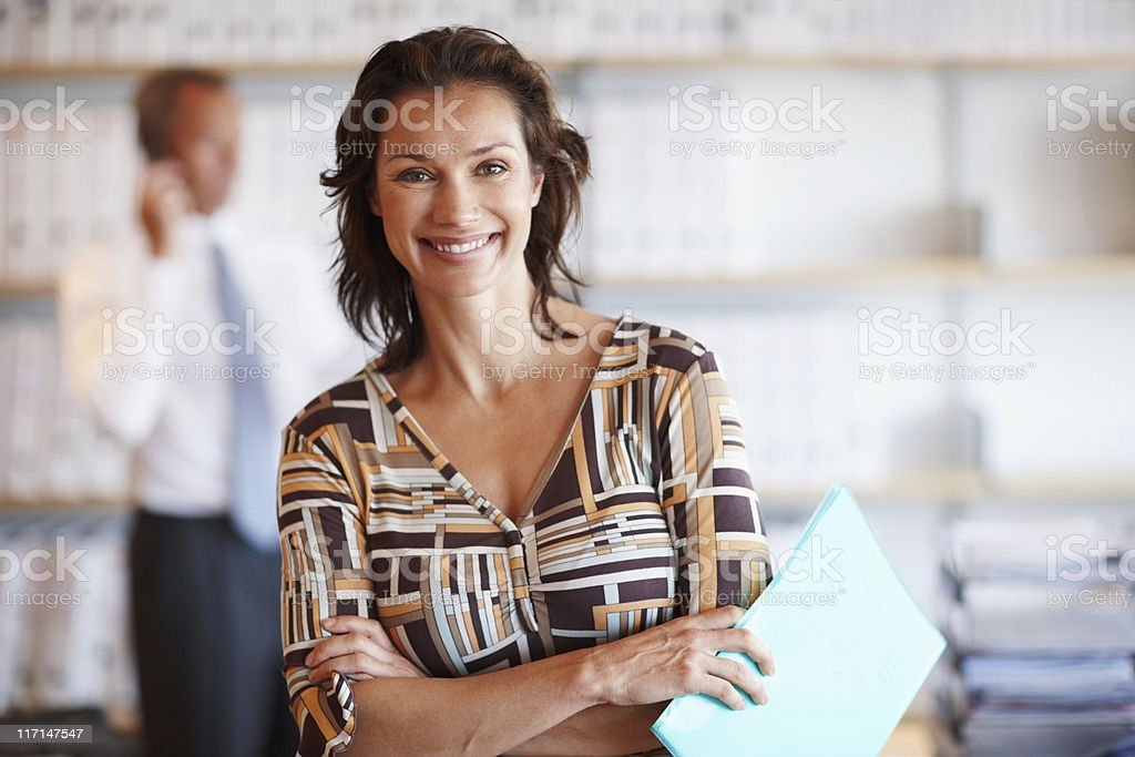 Smiling business woman with male colleague in the background royalty-free stock photo