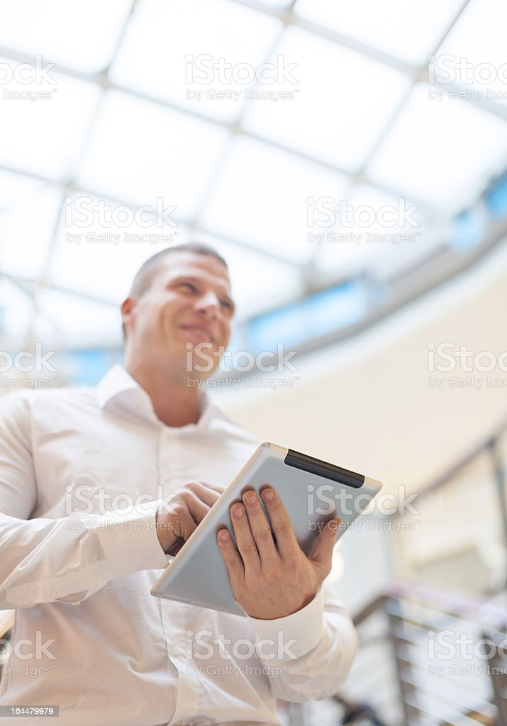 Smiling Businessan with tablet computer in modern business build stock photo