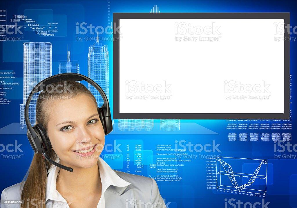 Smiling businesslady in earphones stock photo