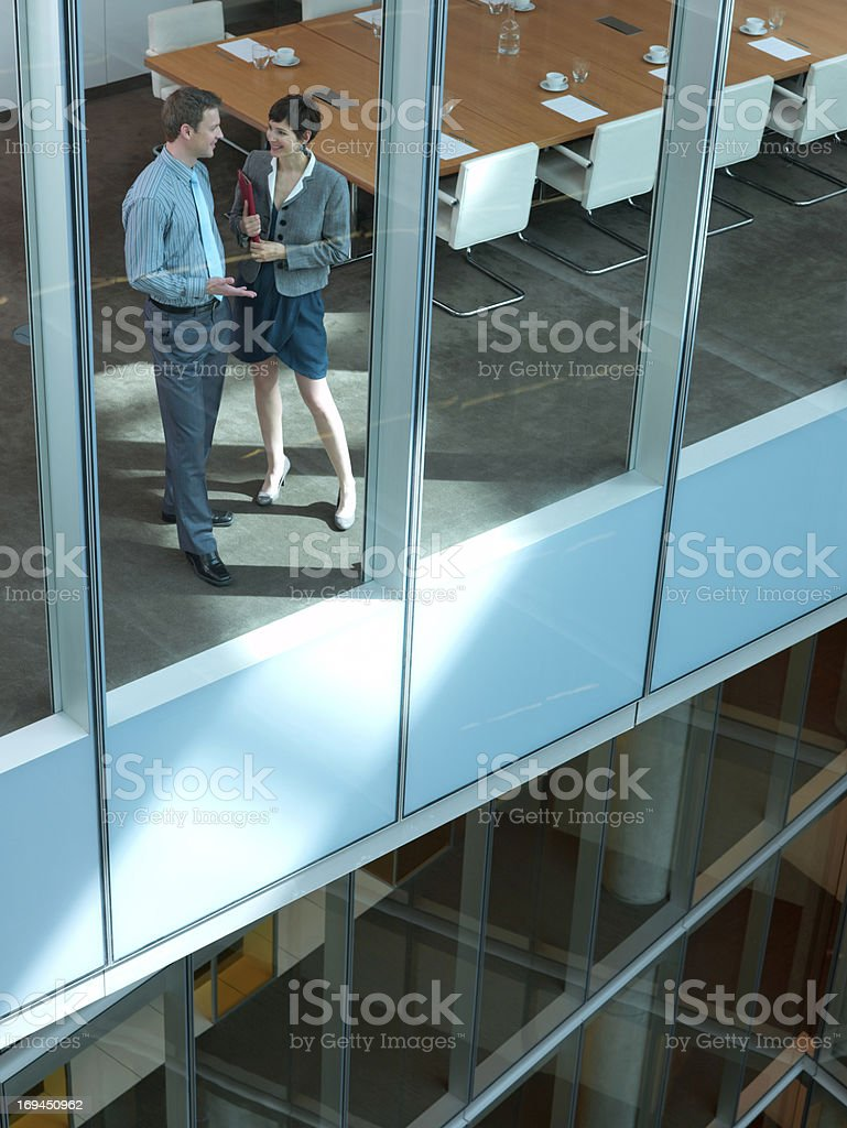 Smiling businessman and businesswoman talking in conference room stock photo