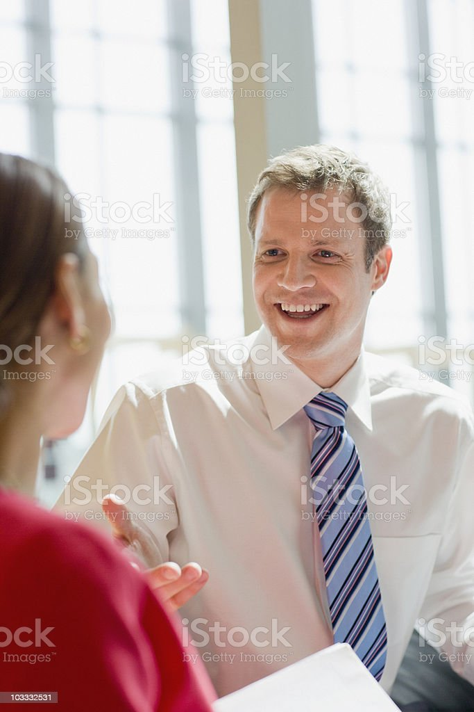 Smiling businessman and businesswoman talking royalty-free stock photo