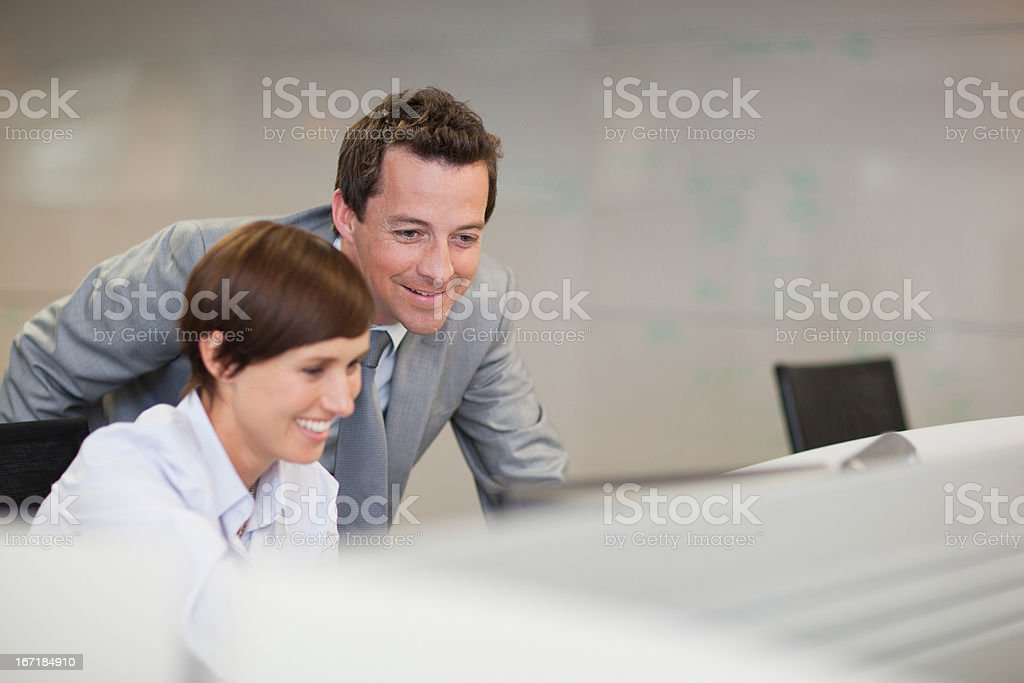 Smiling businessman and businesswoman using computer stock photo