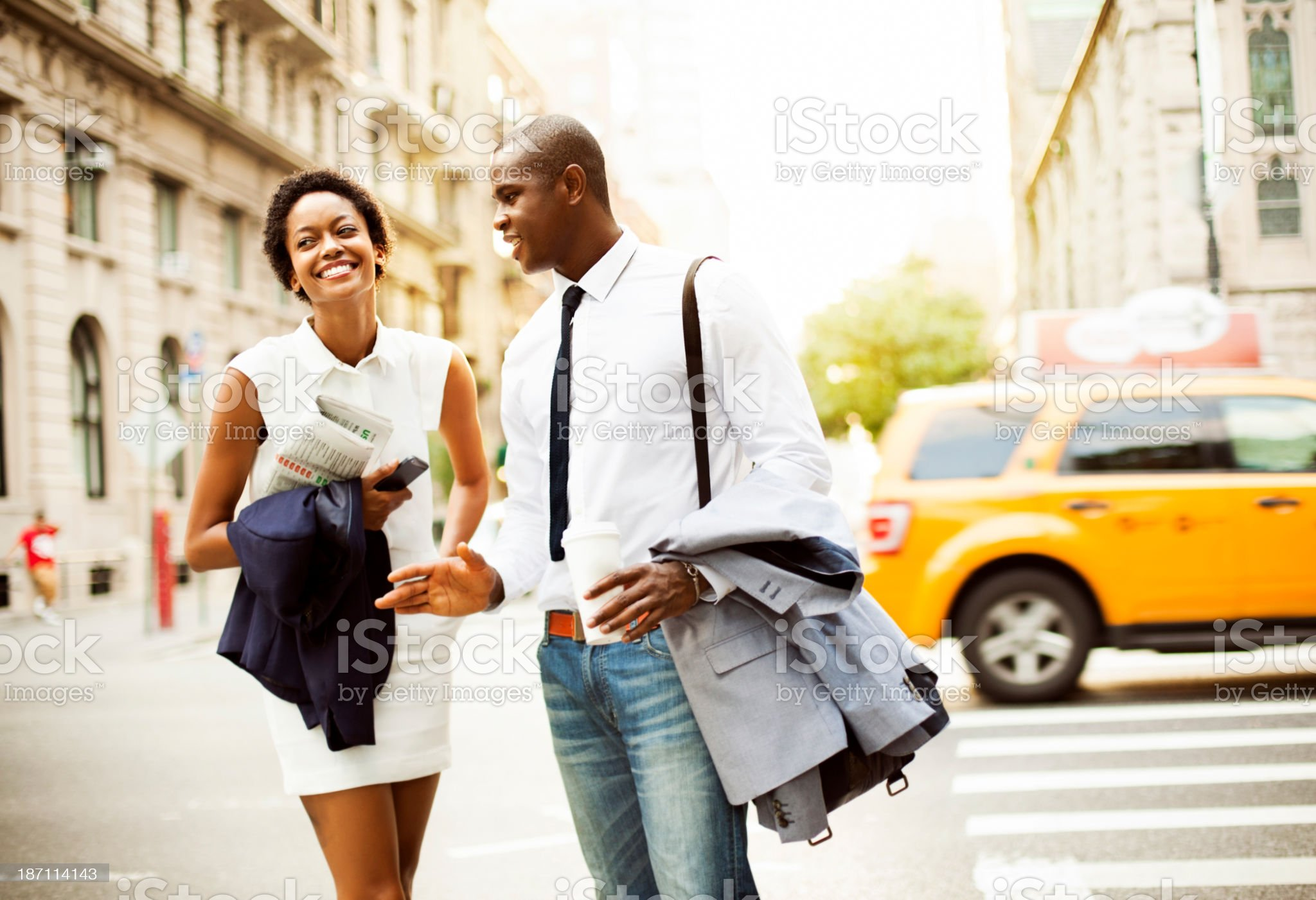 Smiling businessman and businesswoman walking with coffee cups royalty-free stock photo