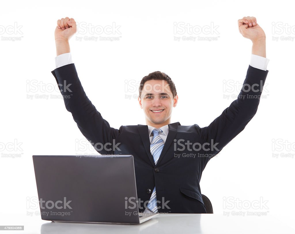 Sonriente hombre de negocios celebrar el éxito de escritorio - foto de stock