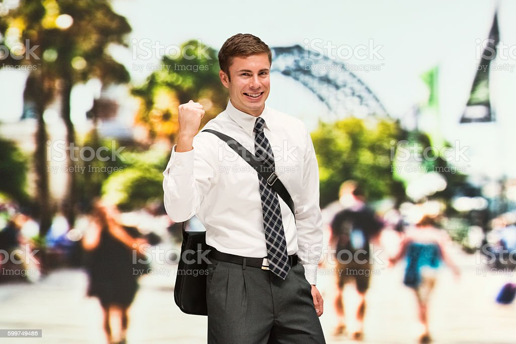 Smiling businessman cheering outdoors stock photo