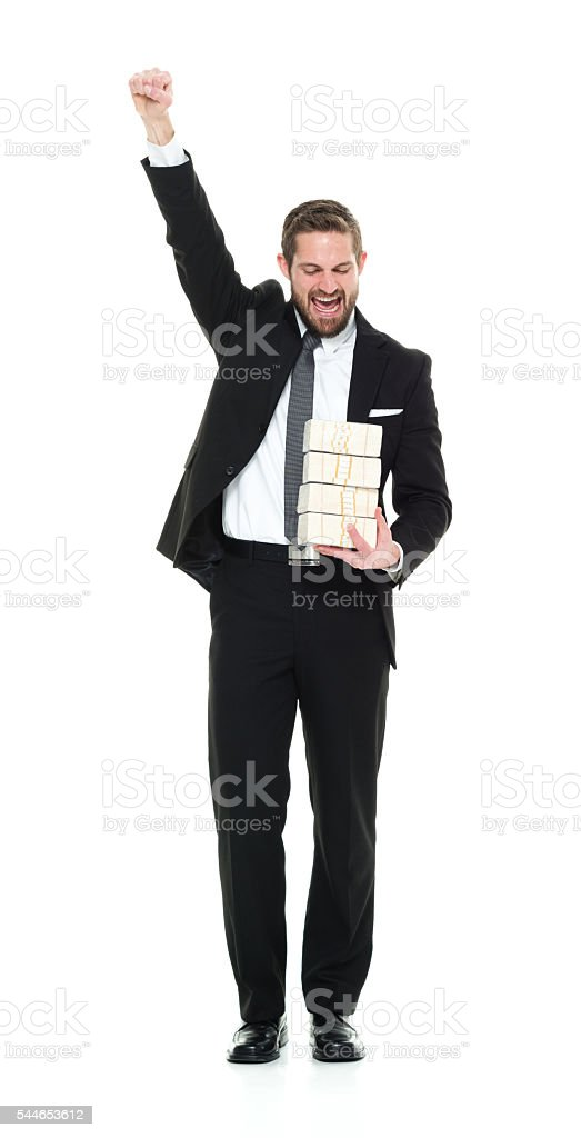 Smiling businessman cheering with money stock photo