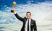 Smiling businessman cheering with trophy
