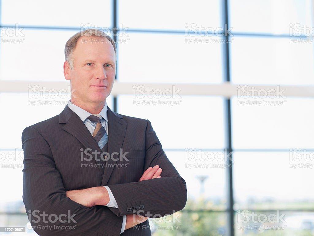 smiling businessman closing arms stock photo
