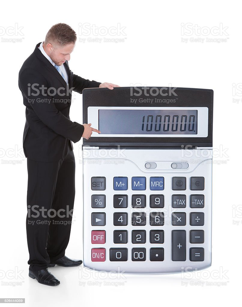 Smiling businessman displaying a calculator stock photo