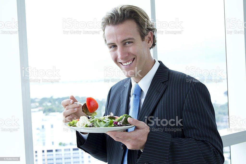 Smiling businessman eating salad stock photo