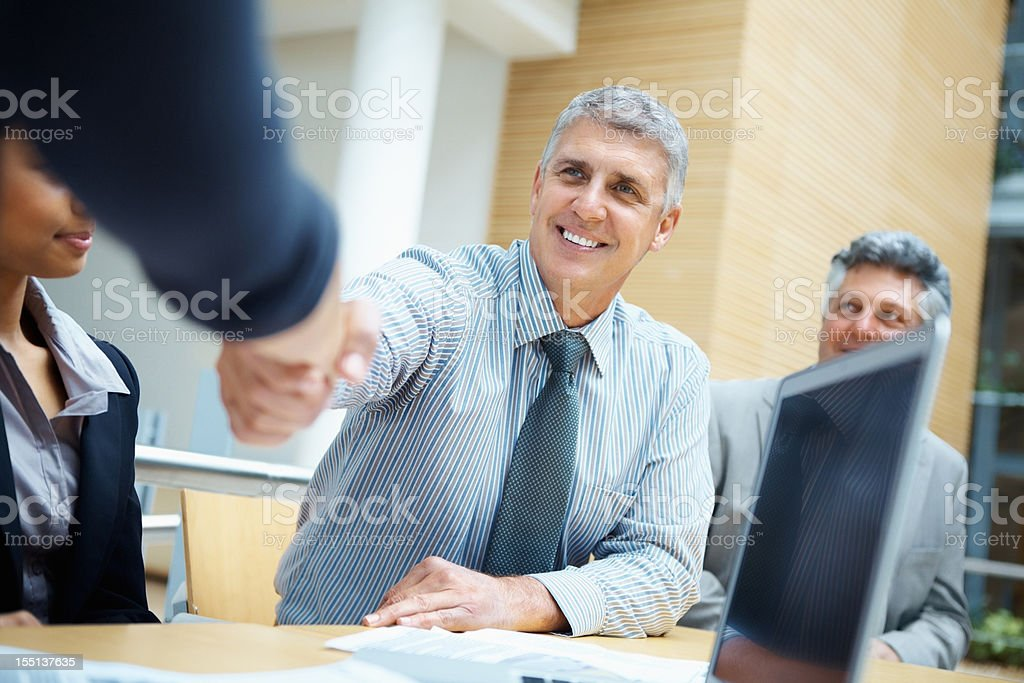 A smiling businessman giving a handshake in an office royalty-free stock photo