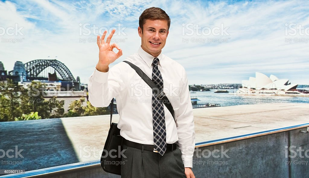 Smiling businessman giving ok sign outdoors stock photo