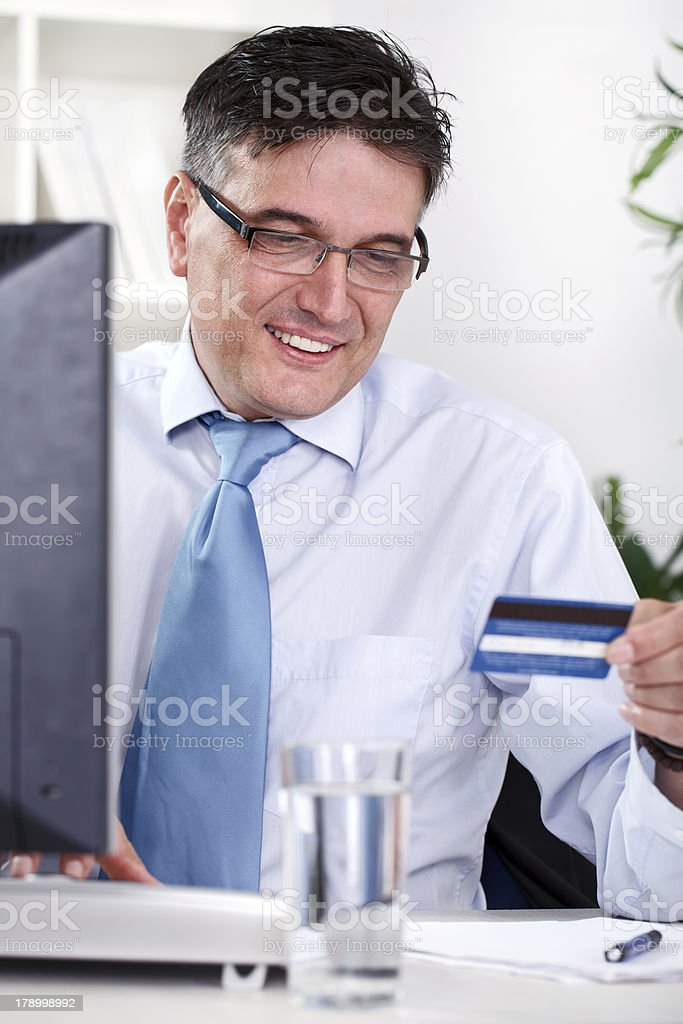 Smiling businessman holding credit card royalty-free stock photo