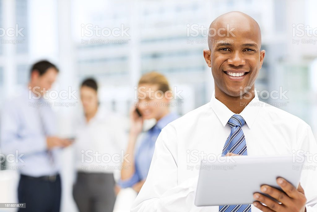 Smiling Businessman Holding Digital Tablet Cohorts In Back royalty-free stock photo