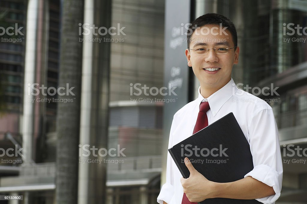 Smiling businessman holding portfolio stock photo