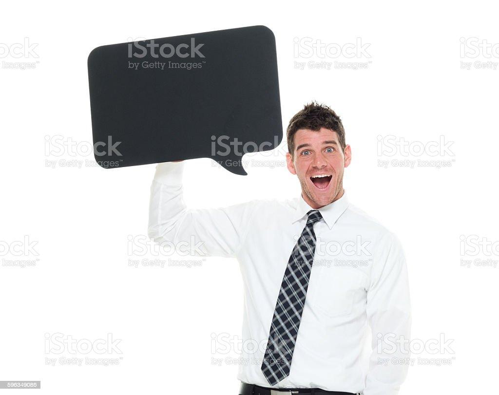 Smiling businessman holding speech bubble stock photo
