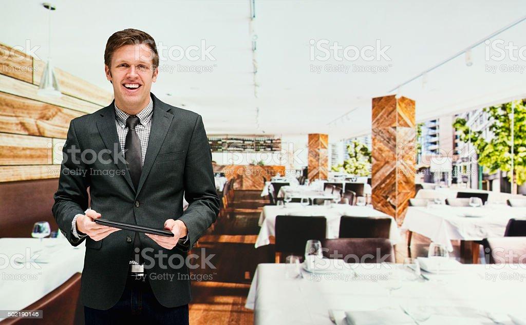 Smiling businessman holding tablet in restaurant stock photo