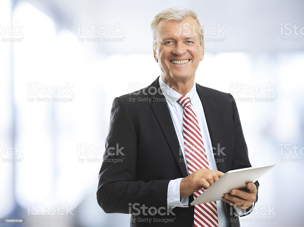 Smiling businessman holding tablet PC stock photo