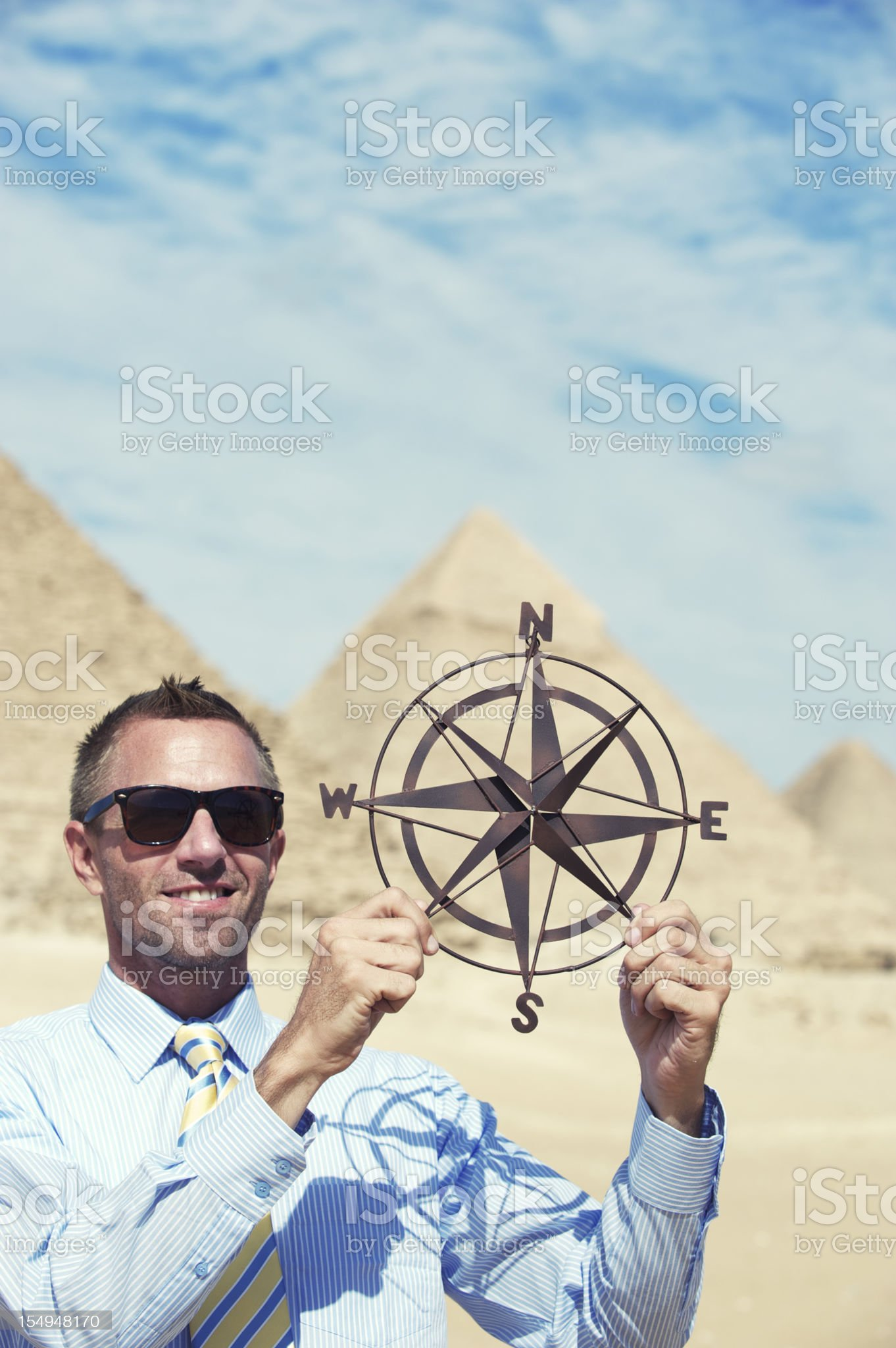 Smiling Businessman Holds Compass by Great Pyramids royalty-free stock photo