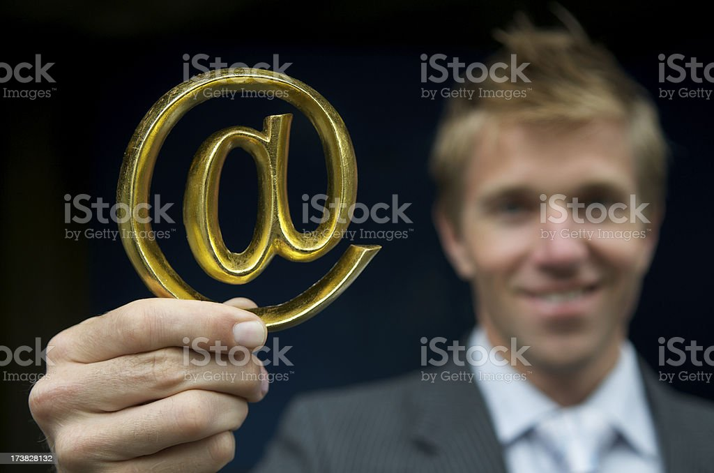 Smiling Businessman Holds Golden @ At Sign royalty-free stock photo