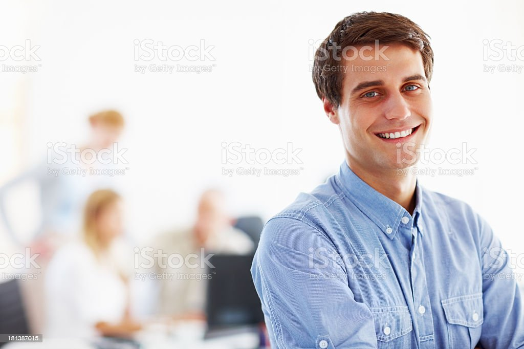 A smiling businessman in a blue shirt, his colleagues nearby royalty-free stock photo