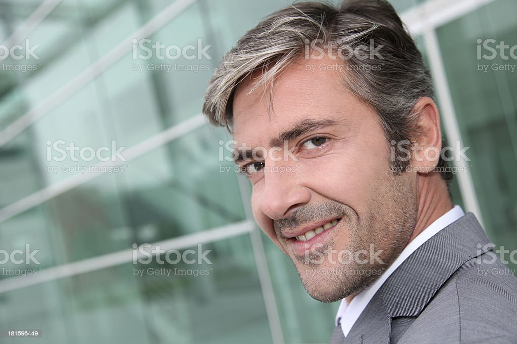 Smiling businessman in front of building glass royalty-free stock photo