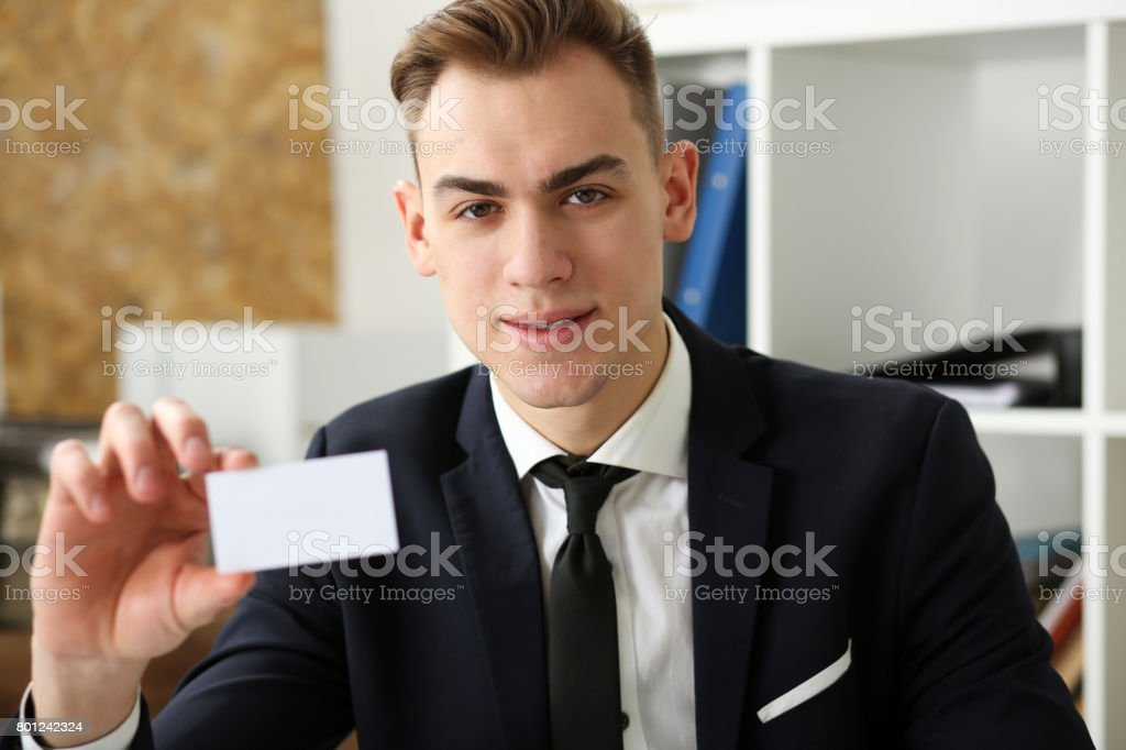 Smiling Businessman in suit hold in hand business card stock photo