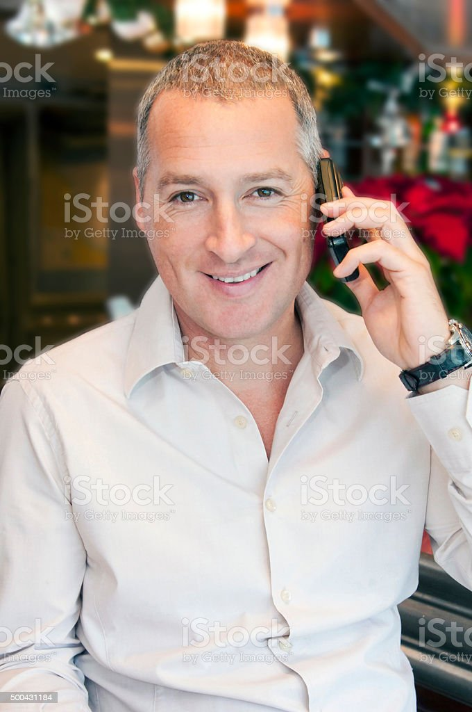 Smiling businessman is speaking on phone sitting in his office stock photo