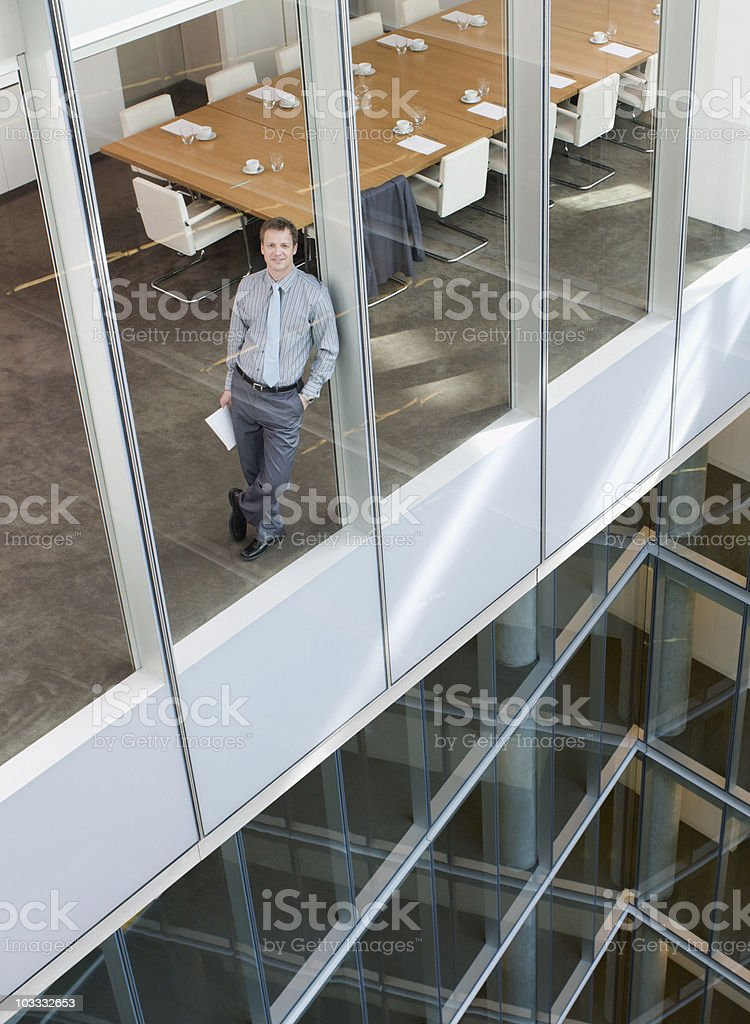 Smiling businessman leaning against window in conference room royalty-free stock photo