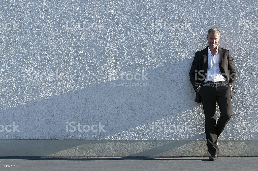 smiling businessman leaning at wall royalty-free stock photo